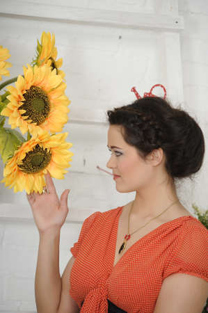 womna: portrait of a young woman next to sunflowers Stock Photo