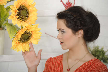 portrait of a young woman next to sunflowers Stock Photo - 17317691