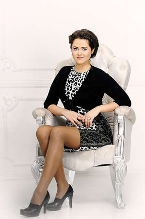 women s legs: Young woman in a chair