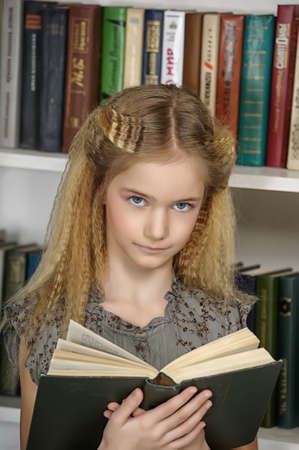 schoolgirl girl with a book on a background library photo