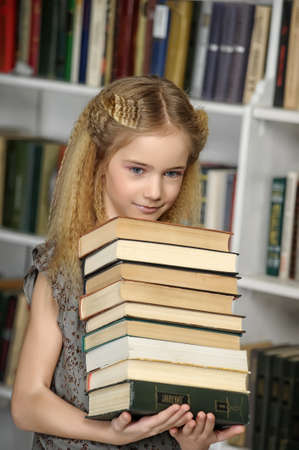 girl holding a pile of books library photo