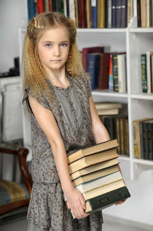 girl holding a pile of books library Stock Photo - 17458471
