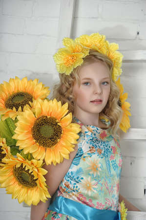 Girl with sunflowers and bright yellow flowers in her hair photo