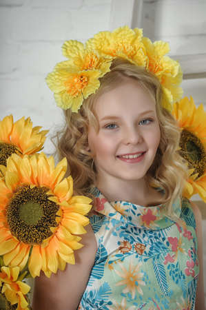Muchacha con girasoles y brillantes flores amarillas en el pelo photo