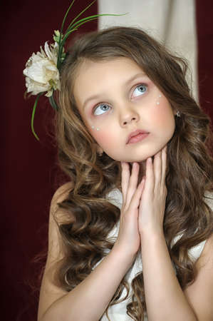portrait of a beautiful girl with curly hair and a flower in her hair photo