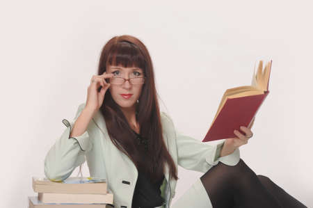 woman with glasses and a pile of books photo