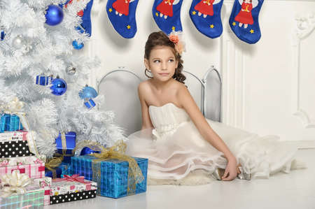 girl in a white dress at the Christmas tree in the living room photo