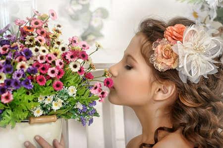 niña y una maceta con flores Foto de archivo