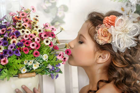 ni�a y una maceta con flores photo
