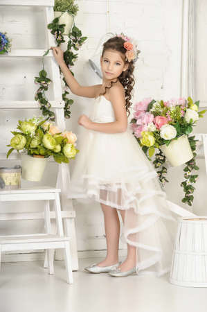 floriculturist: girl in white dress among the flowers Stock Photo
