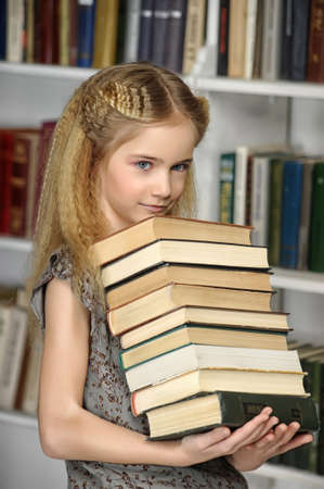 girl holding a pile of books in the library Stock Photo - 17934250