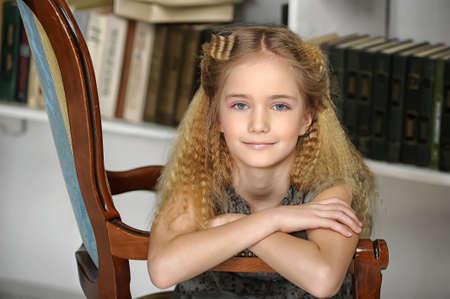 fille dans une chaise contre la bibliothèque