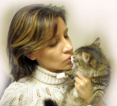 portrait of a woman kissing a cat photo