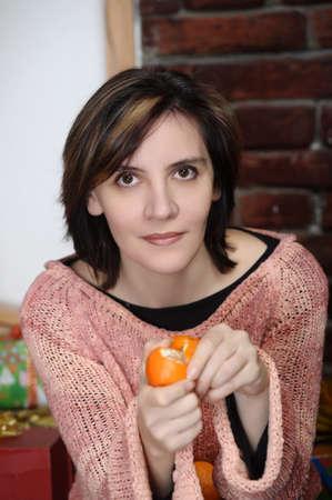 young woman eating mandarin Stock Photo - 17458456