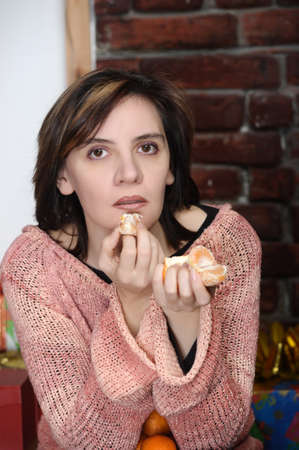 young woman eating mandarin photo