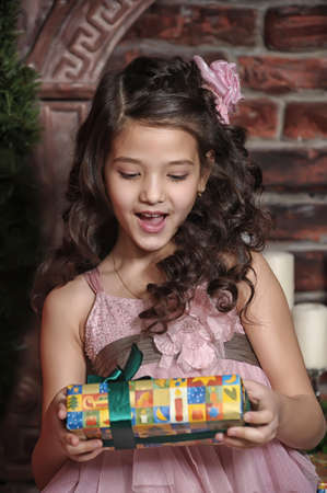 Girl with curly hair with Christmas gifts photo