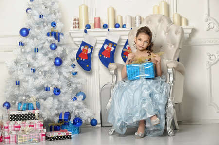 girl with gifts near a Christmas tree Stock Photo - 19026569
