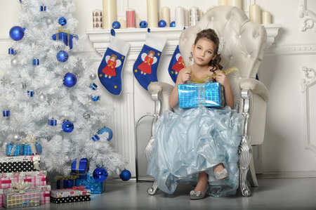 girl with gifts near a Christmas tree photo