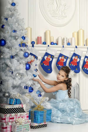 girl with gifts near a Christmas tree Stock Photo