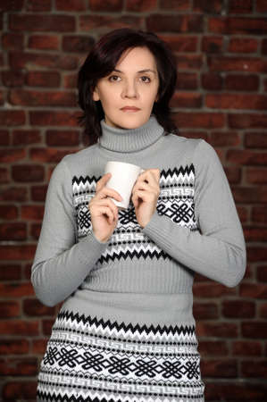 young woman in a gray sweater with a cup in hands Stock Photo - 17962606
