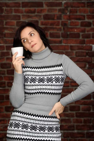 young woman in a gray sweater with a cup in hands photo