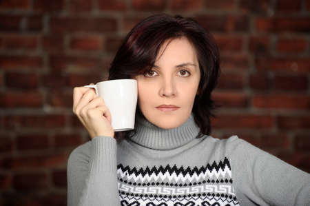 unsmiling: young woman in a gray sweater with a cup in hands