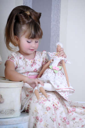 shabby chic background: girl playing with a doll