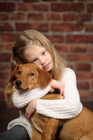 family tickle: girl with red puppy hugs Stock Photo