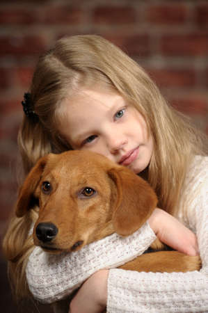brown and black dog face: girl with red puppy hugs Stock Photo