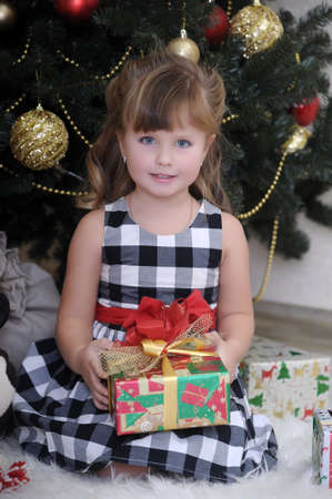 girl with a gift near the Christmas tree Stock Photo - 17934267