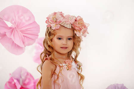 Portrait of a charming little girl with a wreath of roses photo