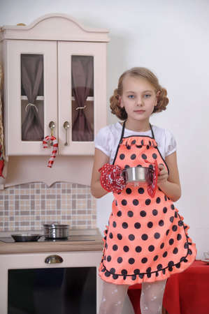 girl in the kitchen with a pan Stock Photo