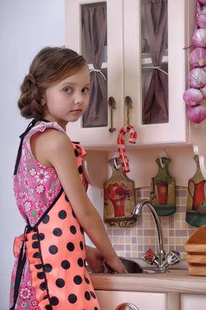 domestic chore: ni�a lavando platos en la cocina Foto de archivo