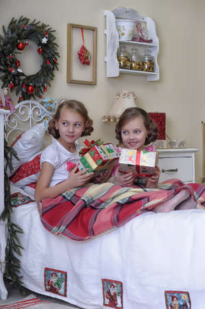 Two girls consider Christmas gifts in the morning in bed photo