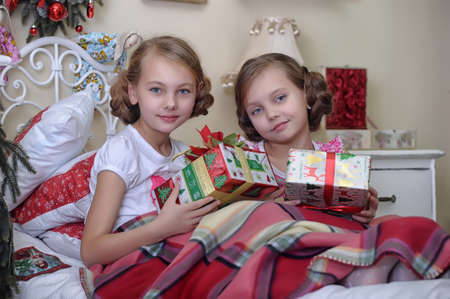 Two girls consider Christmas gifts in the morning in bed Stock Photo - 19139889