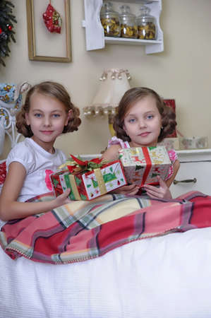 Two girls consider Christmas gifts in the morning in bed Stock Photo - 19139901