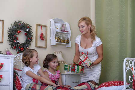 mom gives daughters gifts on Christmas morning photo