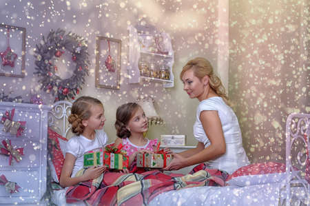 christmas morning: mom gives daughters gifts on Christmas morning