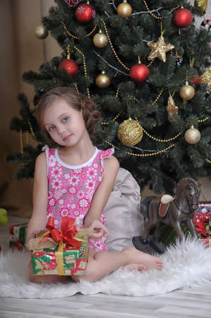 girl with a gift near the Christmas tree Stock Photo - 17935912