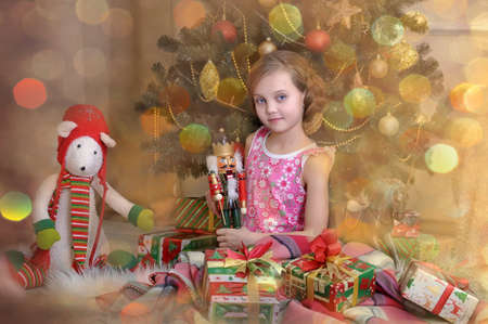 girl with a gift near the Christmas tree photo