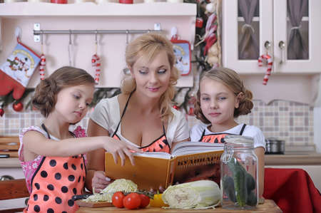 mother with two daughters in the kitchen Stock Photo