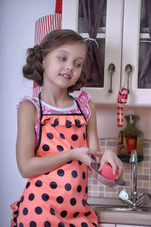 girl washes dishes in the kitchen photo