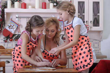 mother with two daughters in the kitchen photo