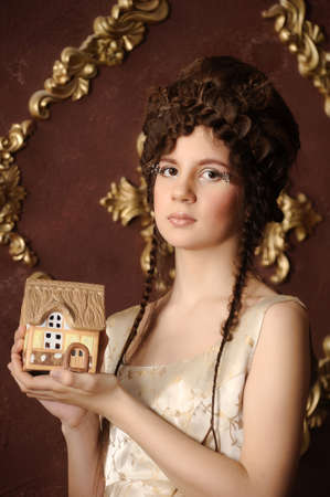 Portrait of a beautiful woman with little house in hands photo