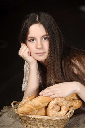 Beautiful girl with bread products in basket photo