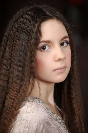 portrait of a beautiful teenager girl with long hair half-turn photo