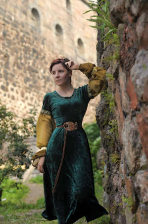 damsel: girl in medieval dress in a castle near a stone wall