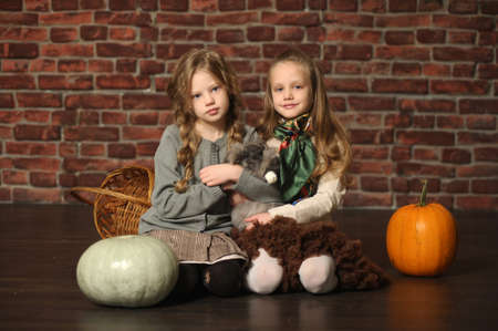 two sisters with a rabbit and pumpkins photo