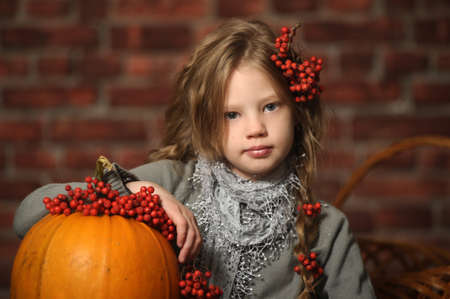 Young girl with a yellow pumpkin photo