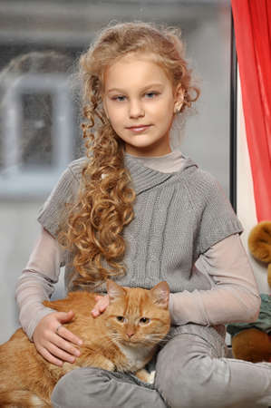 Teen girl with a red cat in her arms photo